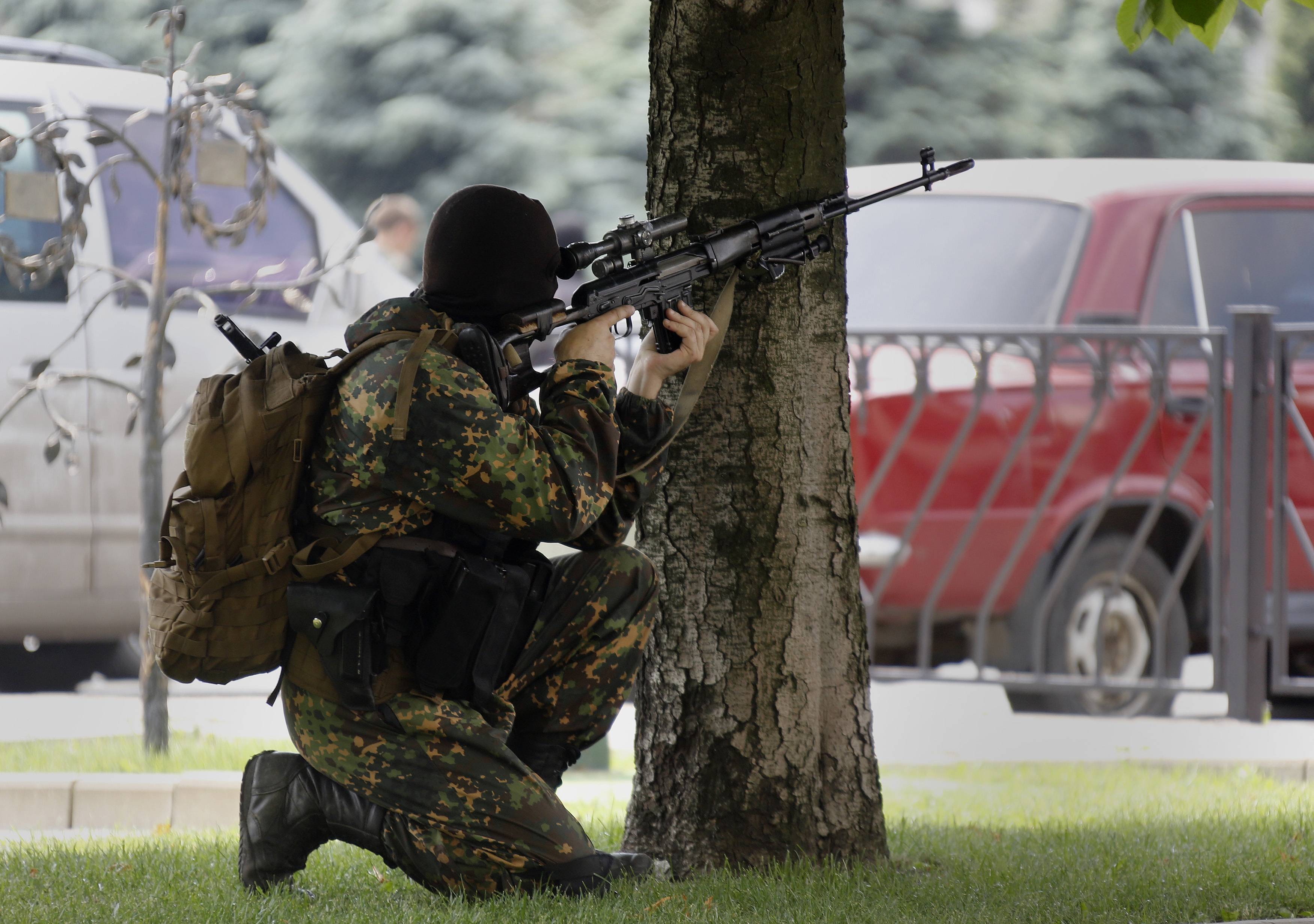 A pro-Russian rebel aims his rifle towards the local administration building in Donetsk
