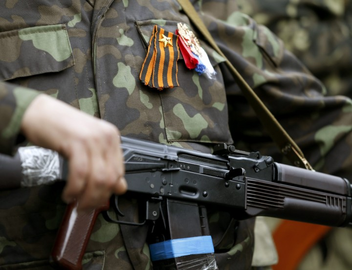 Armed pro-Russian activist holds his weapon as he stands near the seized regional government headquarters in Luhansk