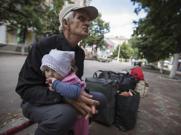 Viktor hold his granddaughter Alissa as they wait for a bus to leave Slaviansk