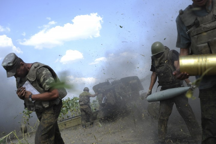 Ukrainian servicemen take cover after firing a cannon during a military operation against pro-Russian separatists near Pervomaisk, Luhansk region