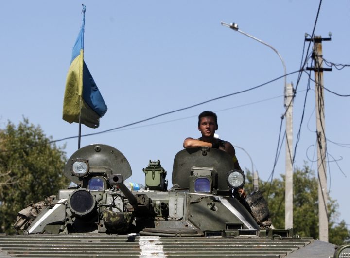 A Ukrainian serviceman sits atop an armoured vehicle as he guards a checkpoint outside Donetsk
