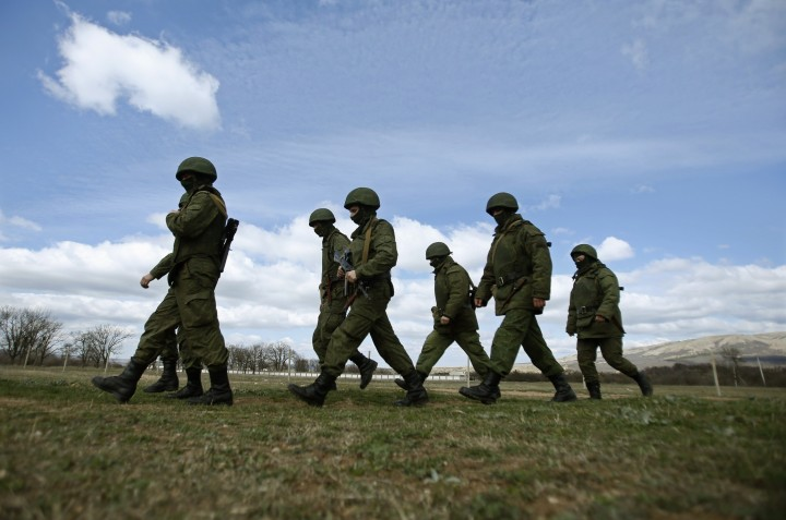 Armed men, believed to be Russian servicemen, march outside an Ukrainian military base in Perevalnoye